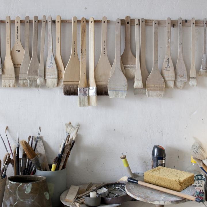 blick auf einen Werkstattplatz mit verschieden Pinseln an der Wand